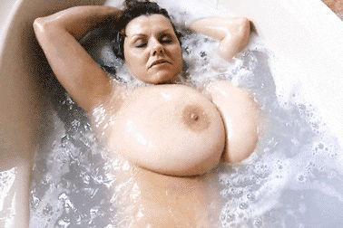 Coroa sacudindo os peitos grandes na banheira